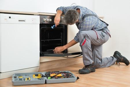 man fixing oven