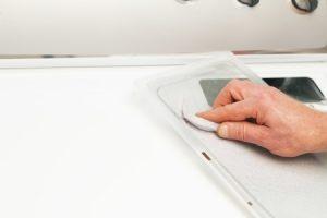 technician cleaning dryer lint filter