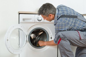 Repairman Checking Washing Machine At Home in houston texas
