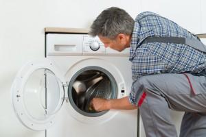 technician Checking Washing Machine At Home