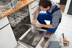 technician fixing dishwasher