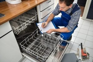 technician sitting near dishwasher writing on clipboard in kitchen