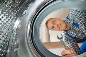 repairman with spanner looking inside the washing machine