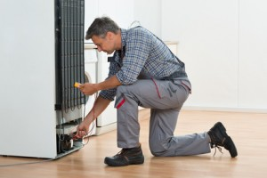 Technician Checking Fridge With Multimeter At Home