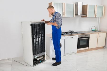 technician repairing refrigerator in kitchen room