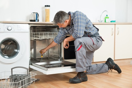 repairman repairing dishwasher