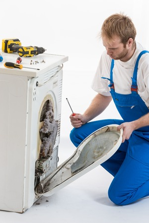 repair man repairing dryer